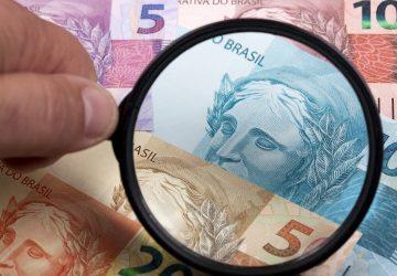lupa sob notas de dinheiro real Brasil para simbolizar a nova lei do superendividamento no Brasil