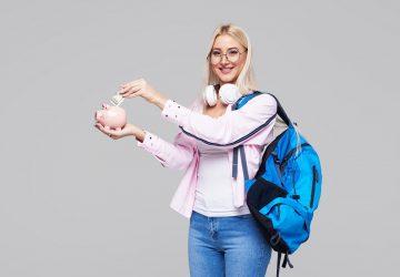 estudante mulher com mochila e fone de ouvido segurando um cofre em formato de porco e colocando dinheiro nele simbolizando dicas financeiras para universitários