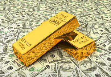 duas barras de ouro sob algumas notas de dólar simbolizando investir em ouro na crise