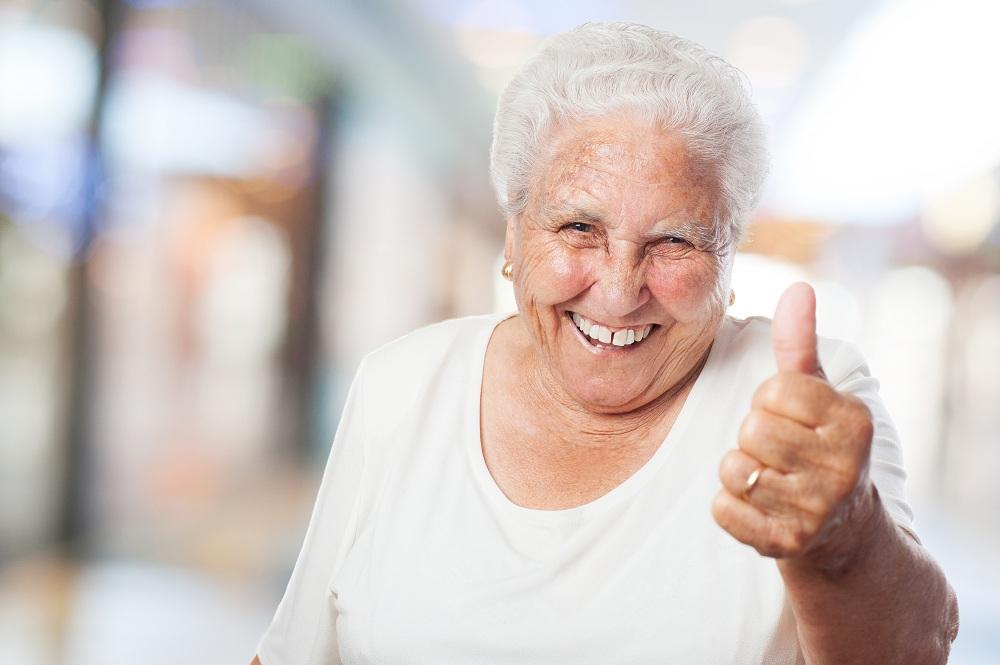 """idosa fazendo """"like"""" dedão para cima em um fundo desfocado"""