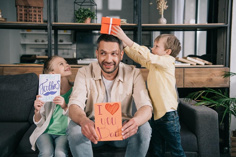 pai em ambiente descontraído recebendo presente do dia dos pais de seus dois filhos pequenos, um menino e uma menina alegres