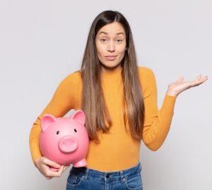 mulher segurando um cofre em formato de porco com semblante de dúvida sobre o que são juros compostos nos investimentos