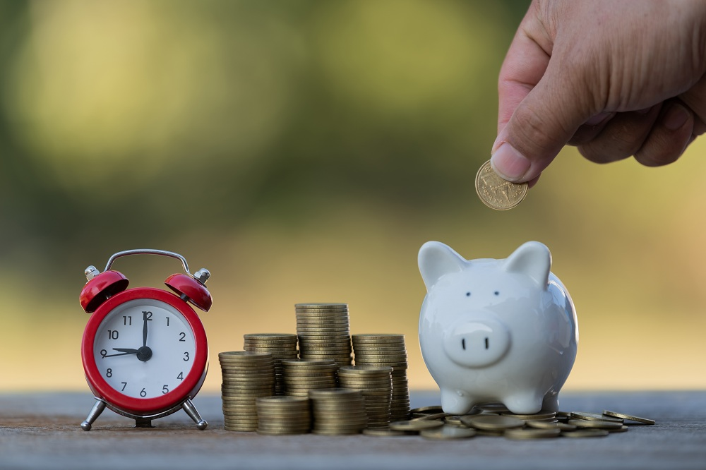 imagem de relógio, moedas empilhadas e uma mão colocando uma moeda em um cofre, simbolizando como economizar dinheiro no dia a dia