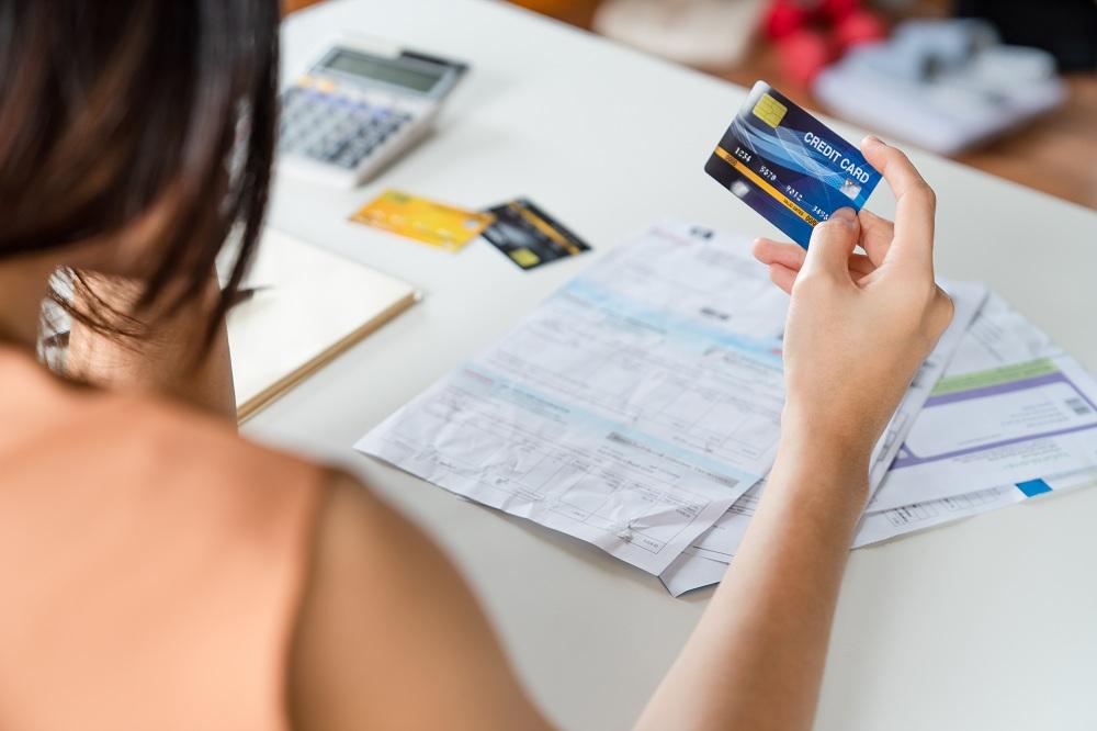 Mulher asiática jovem estressada segurando um cartão de crédito e sem dinheiro para pagar a dívida do cartão de crédito