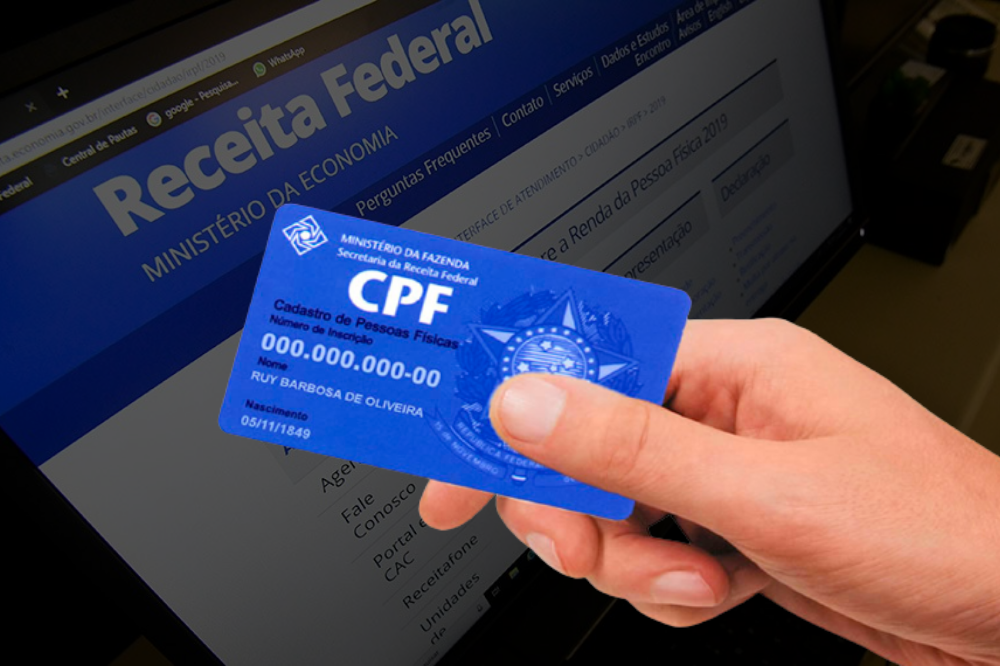 computador ao fundo mostrando o site da Receita Federal e a frente uma mão segurando um cartão de CPF, simbolizando como descobrir o CPF pelo nome
