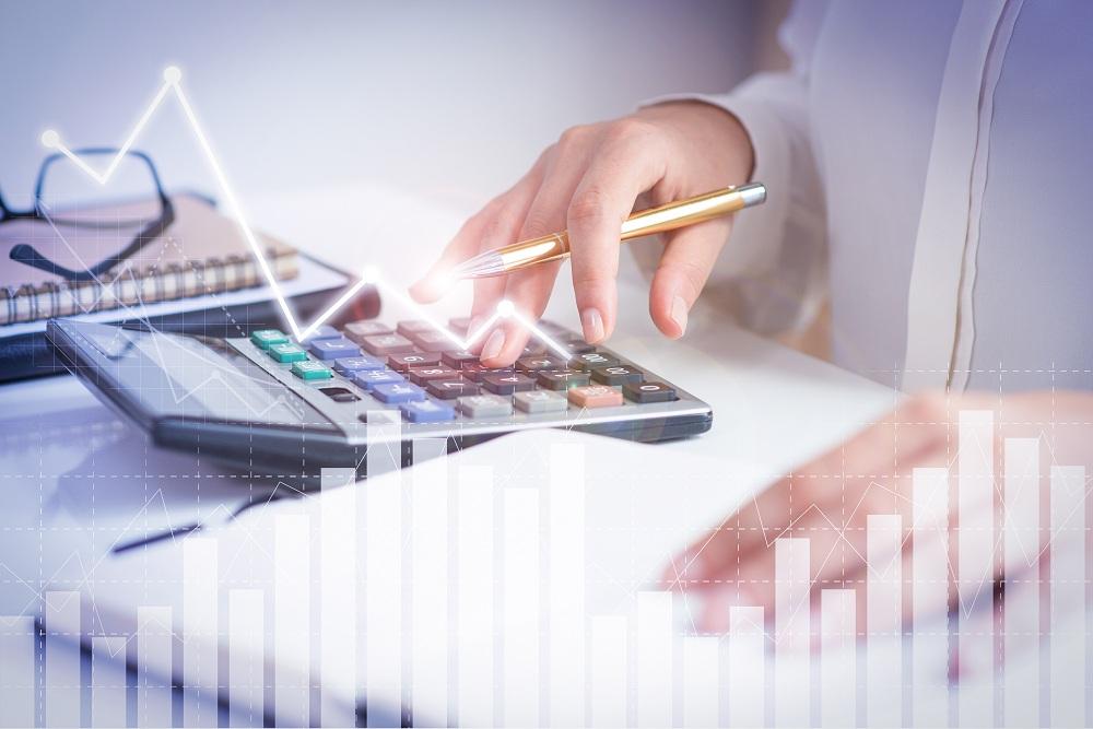 Contador que calcula o lucro com gráficos de análise financeira simbolizando o investimento em renda fixa ou variável
