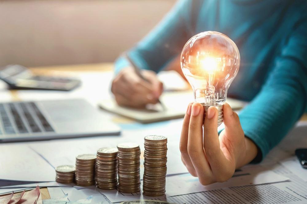 mão de mulher segurando lâmpada e fazendo cálculos, simbolizando um empréstimo na conta de luz como fazer