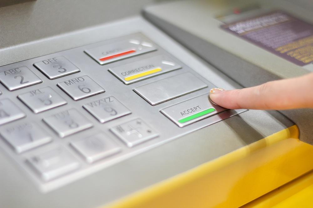 imagem de mulher apertando o botão de confirmar de um caixa eletrônico simbolizando o empréstimo no caixa