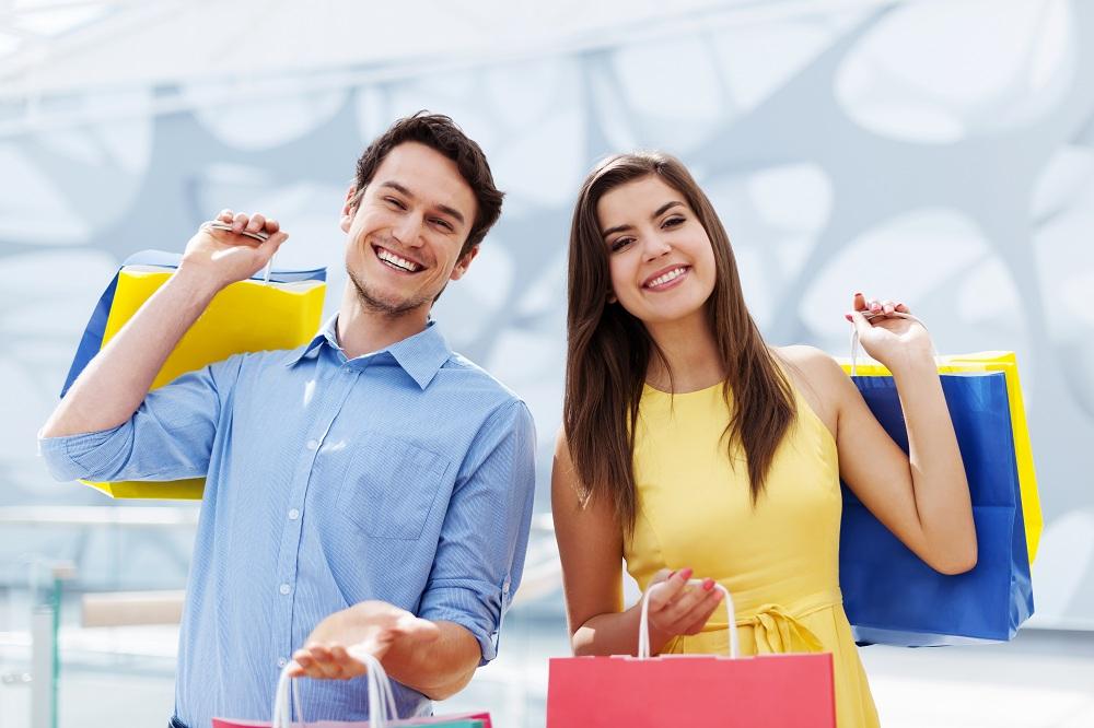 Jovem casal feliz segurando uma sacola de compras que pagaram no crediário