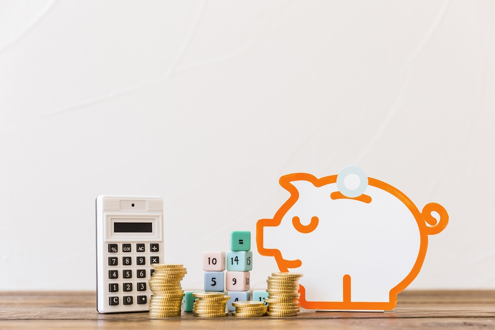 imagem com calculadora, moedas e cofre de moedas para ilustrar o que é o que é e como funciona a conta poupança