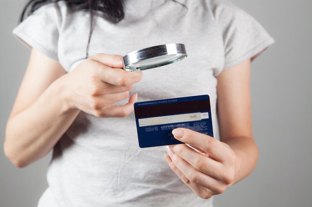 Mulher olhando para um cartão de banco com uma lupa para tentar descobrir os números do cartão de crédito