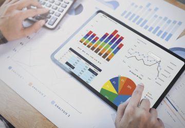 Mulher de negócios usando um tablet para analisar o conceito de sucesso de estatísticas de estratégia de finanças de empresa e planejamento para o futuro na sala de escritório