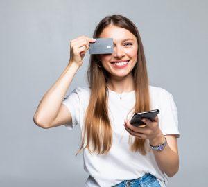 Mulher jovem e animada com telefone celular e cartão de crédito
