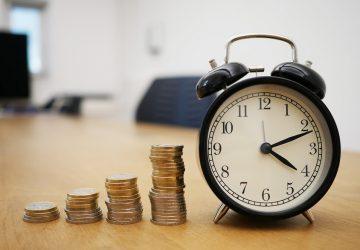 moedas empilhadas de forma crescente ao lado de um relógio em cima de uma mesa de escritório simbolizando a rentabilidade dos investimentos com a Selic em alta