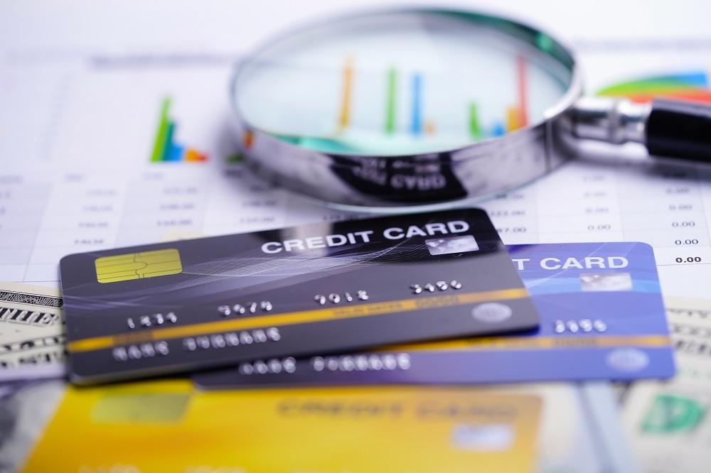 três cartões de crédito em cima de uma mesa com planilha de resultados e uma lupa simbolizando dicas de como usar o cartão de crédito sem se endividar