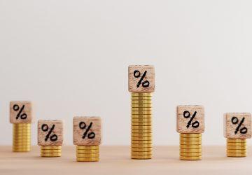 moedas empilhas e em cima blocos de madeira com símbolo de porcentagem, simbolizando o que é e como funcionam as taxas de juros no Brasil