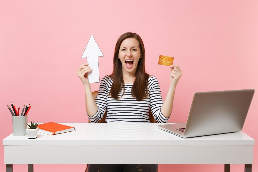 mulher jovem com uma ceta apontando para cima em uma mão e na outra um cartão, com cara de felicidade, simbolizando as Dicas para aumentar o limite do cartão de crédito