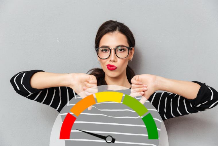 mulher de óculos com aspecto facial descontente apontando as duas mãos para baixo, onde tem uma escola de poontuação marcando o vermelho, simbolizando os Hábitos que diminuem o score