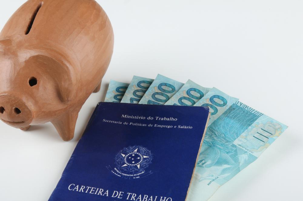 carteira de trabalho brasileira com notas de cem reais dentro e ao lado um cofre em formato de porco de madeira, simbolizando o investimento em um plano de previdência privada para a aposentadoria