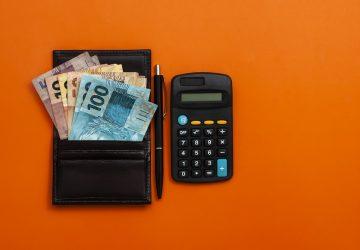 fundo laranja e na imagem uma carteira com notas de cem, cinquenta, vinte e dez reais e ao lado uma caneta e calculador simulando o quanto investir todos os meses