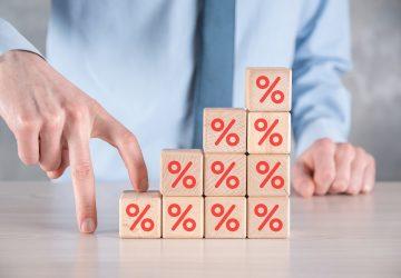 bloquinhos de madeira empilhados de forma crescente com desenho do símbolo de porcentagem em vermelho simbolizando o que são juros compostos como afetam nossa vida financeira