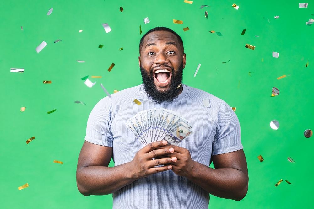 homem feliz e estonteante segurando dinheiro na mão simbolizando como ganhar dinheiro com aplicativos de recompensa